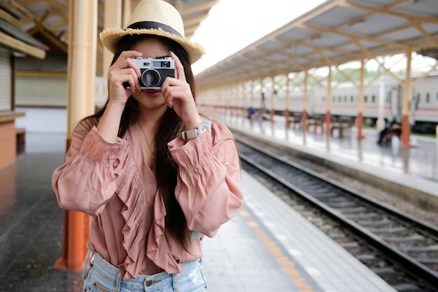 駅で写真を撮るカメラを保持している女性旅行者