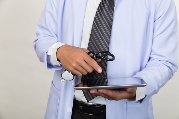 医者は聴診器を押しながら現代のタブレットコンピューターでの作業