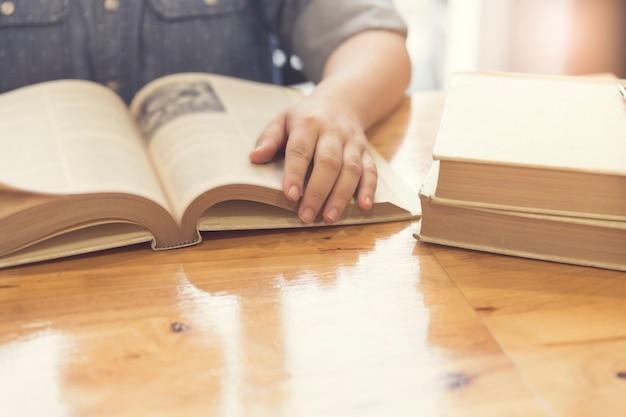 木製のテーブル、セレクティブフォーカス、ビンテージトーンの本を読む女性の手