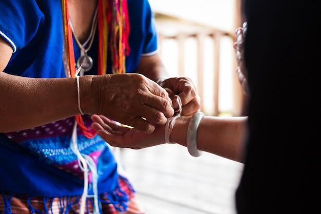 Неизвестная пожилая женщина из этнического меньшинства карена связывает запястье гостя благословением на церемонии обвязки