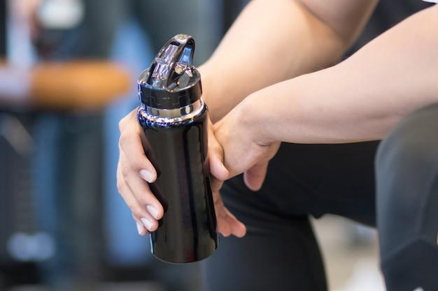 若い男は、フィットネスセンターで飲料水のボトルを保持します。