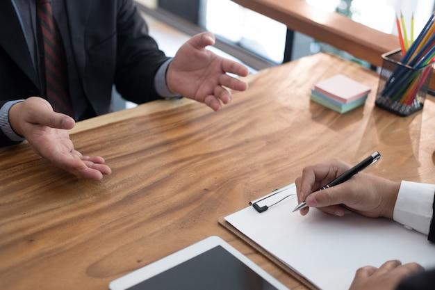 ビジネスの欠員のための就職の面接で候補者に話しているビジネスマン。