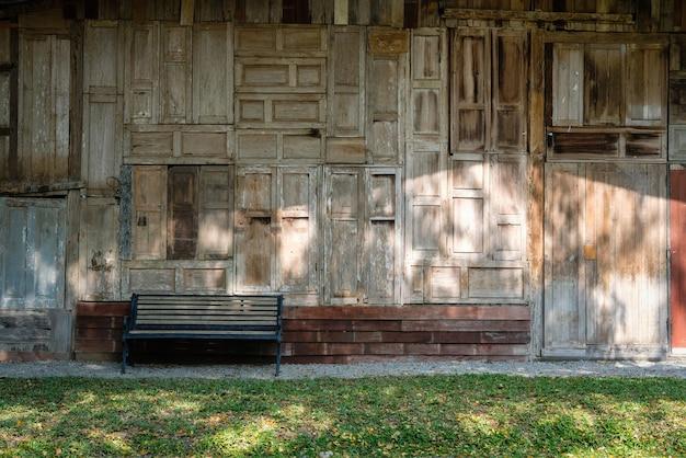 古い木の家の横にある木製のベンチ。