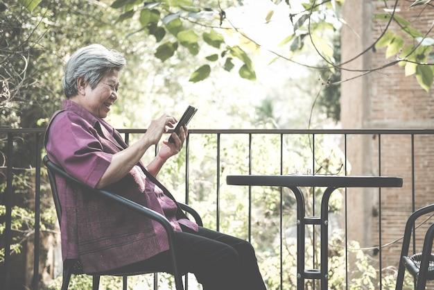 Старшая женщина держит мобильный телефон на террасе.