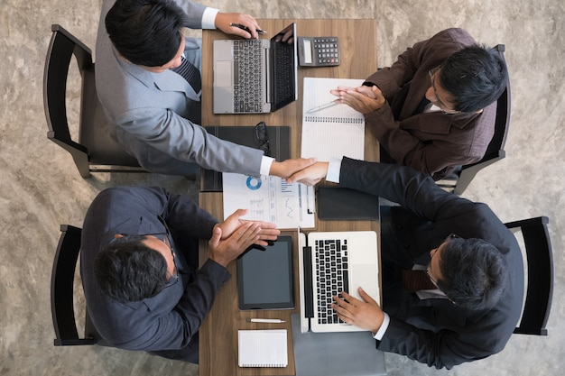 会議を終えた後に握手するビジネス人々