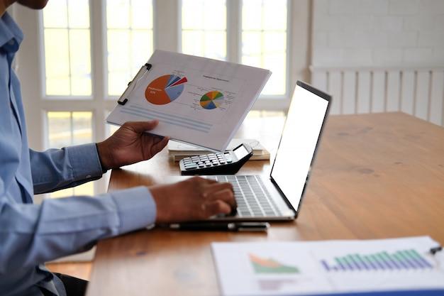 ドキュメントで作業するビジネスマン、スタートアップ男は職場での財務データを分析します。