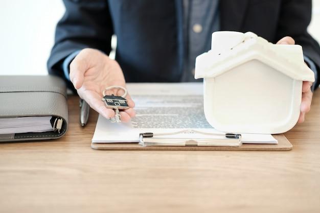 家のモデルと家の鍵を持つ不動産業者、賃貸不動産の購入
