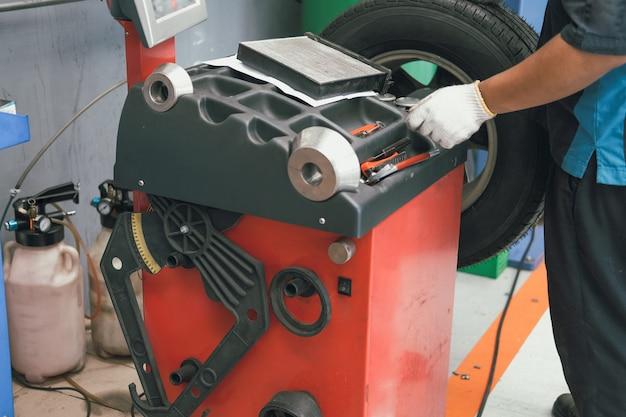 自動車修理ガレージで重量をバランスさせるためにタイヤを回転させるための車のホイールバランシングマシン