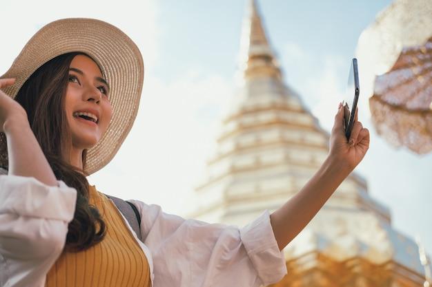女性は写真を撮るためにスマートフォンを使用します。旅行者の観光は、休暇に旅行します。旅の旅