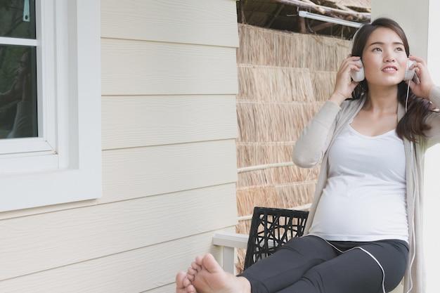 Молодая азиатская женщина сидя на балконе слушая к музыке усмехаясь с удовольствием