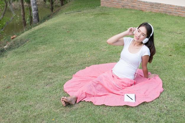 音楽を聴くと喜びで笑顔の新鮮な春の草に座っている若いアジア女性。