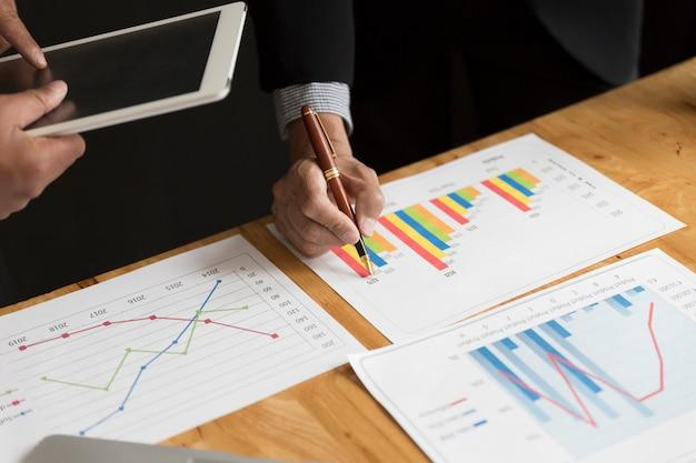 スーツのビジネスマンが市場分析ビジネスグラフを分析します。