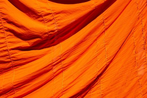 背景の仏教の僧侶や初心者のオレンジ色のローブのテクスチャ