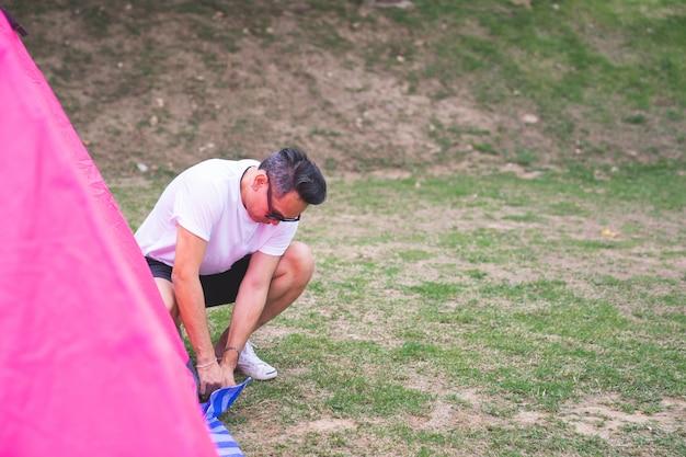 Азиатский мужчина в белой футболке устанавливает розовую палатку у кемпинга