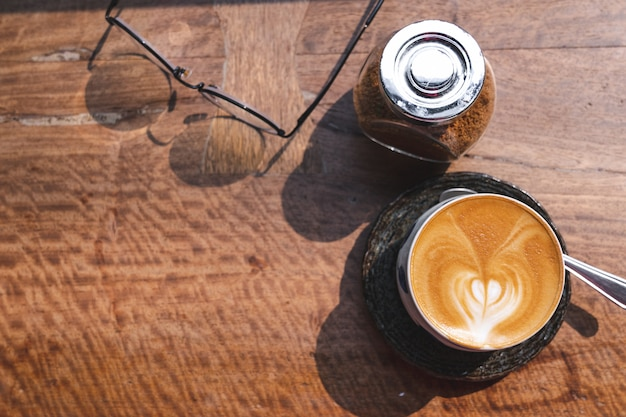 朝の光の中で木製の机の上のラテアート、メガネとブラウンシュガーとホットミルクコーヒーのカップのトップビュー