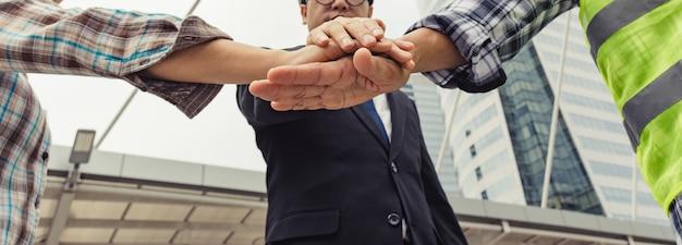 ビジネスマンとエンジニアが手を組み、成功するプロジェクトを構築します。チームワークの概念。