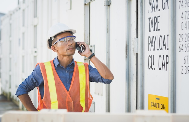 Тайский красивый инженер человек, стоящий на телефоне перед контейнером.