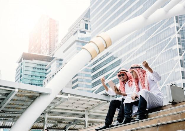 Два молодых арабских бизнесмена поднимают руки, чтобы выразить благодарность за успешные деловые переговоры и прибыльный бизнес.