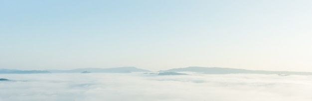 朝は白い霧の山々の美しい風景。