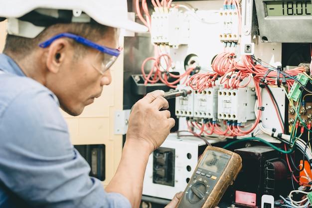 エンジニアは、冷蔵コンテナ電源システムの電気回路をチェックしています。