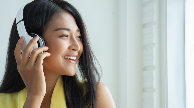 美しいタイの女性は、ワイヤレスヘッドフォンからのリスニングを楽しんでいます。
