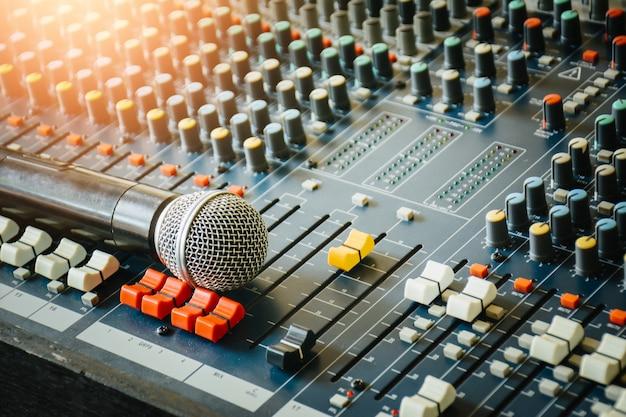 Беспроводные микрофоны размещены на аудиомикшере, чтобы контролировать использование связей с общественностью в конференц-зале.