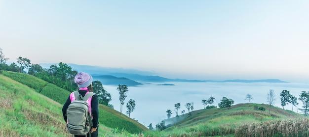 アジアの女性観光客が立って、朝の山の風景と日の出を見て。
