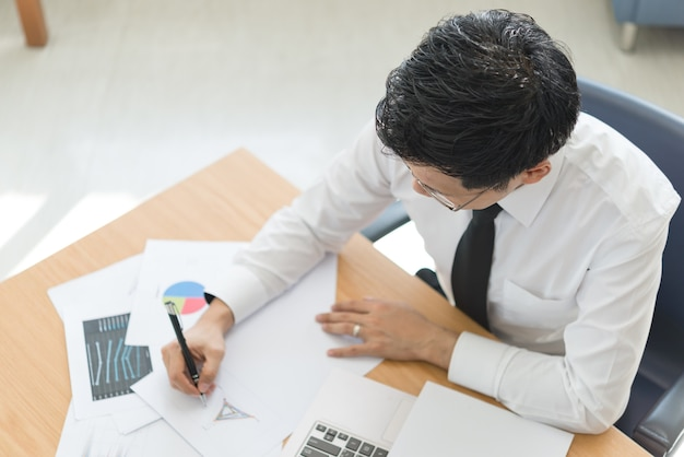 若いビジネスマンは、明るい日差し、明るい部屋、晴れた日、笑顔でオフィスで働いています