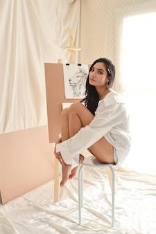 鉛筆(女性のライフスタイルコンセプト)で絵を描きながら休憩を取って白いシャツのアジア女性アーティスト
