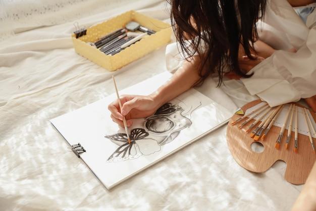 女性アーティストは、応接室(女性のライフスタイルのコンセプト)で鉛筆で白いシャツの絵を描く