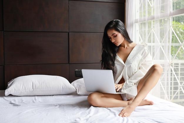 Платье взрослой внештатной азиатской сексуальной женщины нося белое работая на компьютере пока сидящ на кровати в спальне