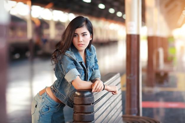 電車を待っているジャケットジーンズを持つ若い旅行者女性