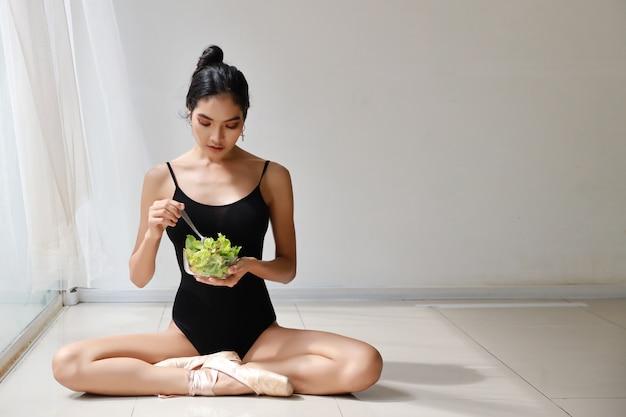 美しい健康的でスポーティなアジアの若い女性サラダボウルを保持し、トレーニング後に食べる