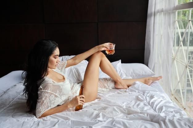 飲酒と寝室のベッドの上に横たわっている間アルコール飲料のボトルを保持している白いランジェリーで酒に酔ったアジア女性