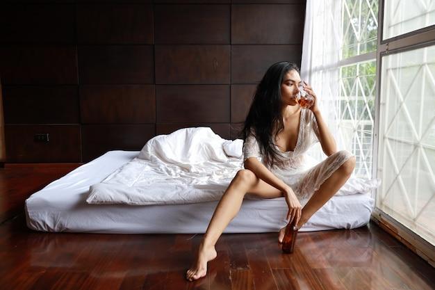 Пьяная азиатская женщина в белом белье, пьющая и держащая бутылку спиртного, сидя на кровати в спальне