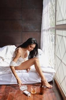Полная длина пьяная азиатская женщина в белом белье, пить и курить, держа бутылку спиртного и сидя на кровати в спальне