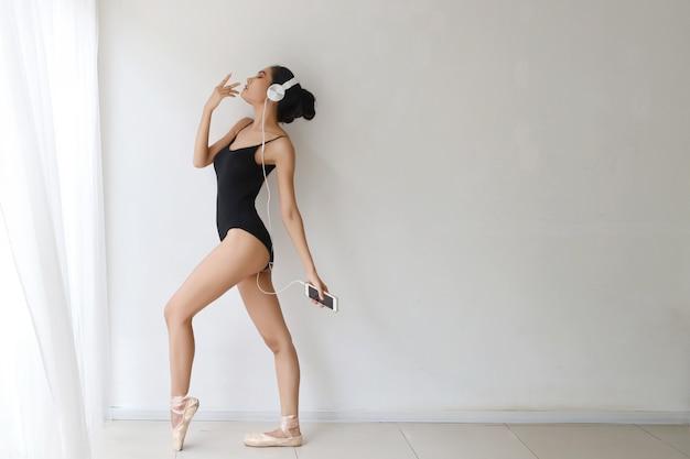 ヘッドフォンから音楽を聴きながらスマートフォンでバレエを練習して、スポーティで健康的な若い美人顔を持つ若い女性