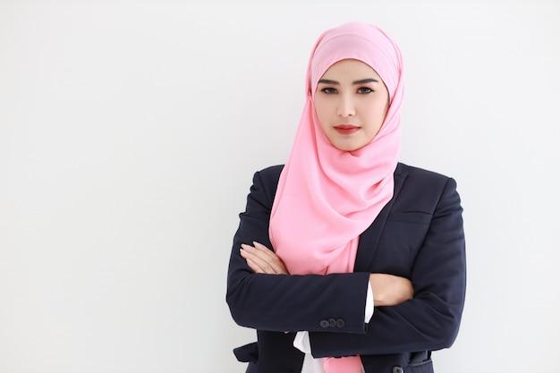 Довольно мусульманская молодая азиатская женщина нося голубой костюм усмехаясь уверенно