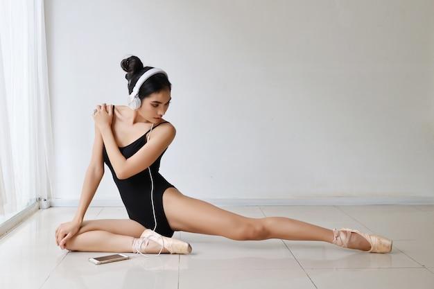 ヘッドフォンで座っている黒いスポーツウェアを着て魅力的なアジアの女性の見事な形。美しい女性がバレエダンスをトレーニングしながら携帯電話から音楽を聴く