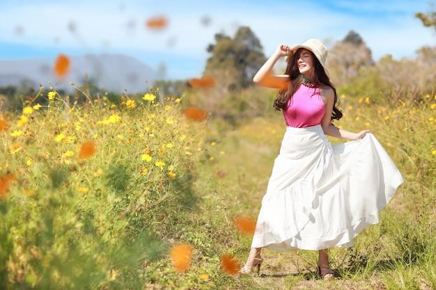 アジアの美しい女性、青い空と山と冬に提出された黄色のコスモスにピンクのドレスの長い髪。