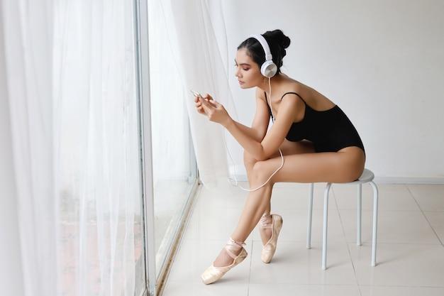 Сногсшибательная форма очаровательной азиатской женщины нося черную спортивную одежду сидя с наушниками. красивая женщина прослушивания музыки с мобильного телефона во время тренировки балета