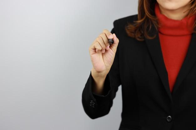 ビジネスの女性は黒と赤のビジネススーツを着て制服ペンを保持していると自信を持って何かを描く