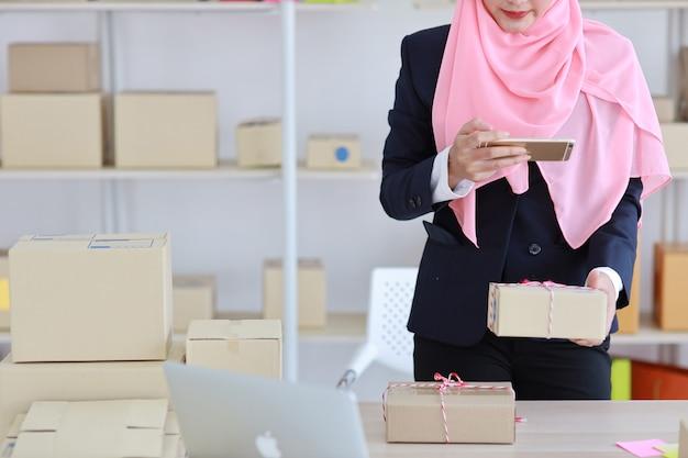 携帯電話から配信パッケージパッケージの立っていると写真を撮る青いスーツで宗教的なアジアのイスラム教徒の女性を閉じます。