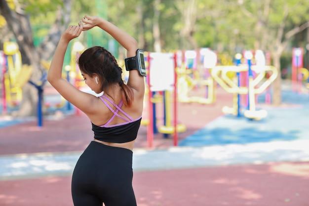 Концепция образа жизни общественного упражнения, фитнес женщина прослушивания музыки от беспроводных наушников и мобильного телефона. девушка заднего вида атлетическая молодая азиатская в положении спортивной одежды, протягивая после тренировки
