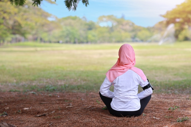 Вид сзади молодая азиатская мусульманская женщина сидя на траве, наслаждаясь раздумьем. мирная девушка в спортивной одежде с розовой хиджаб практикуют йогу в природе зеленые деревья с миром и спокойствием. здоровая и спортивная концепция