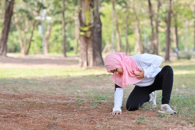 Красивая молодая азиатская мусульманская девушка в спортивной одежде держит обе руки на груди или груди и боль после длительной тренировки. фитнес женщина проблемы с дыханием и чувство сердечного приступа. медицинская и спортивная концепция