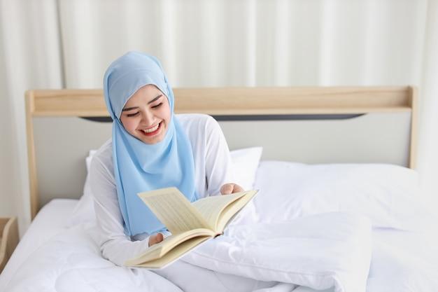 Счастливая молодая красивая азиатская мусульманская женщина в усаживании пижамы, книге чтения на кровати. жизнерадостная и милая девушка отдыхает в спальне с улыбающееся лицо и копией пространства для вашего рекламного контента.