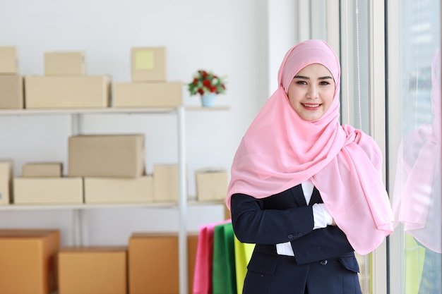 Религиозная азиатская мусульманская женщина в голубом костюме и розовом валу на голове стоя и смотря на камеру с уверенностью. стойка бизнес-леди с предпосылкой поставки коробки мсп пакета. концепция работы на дому