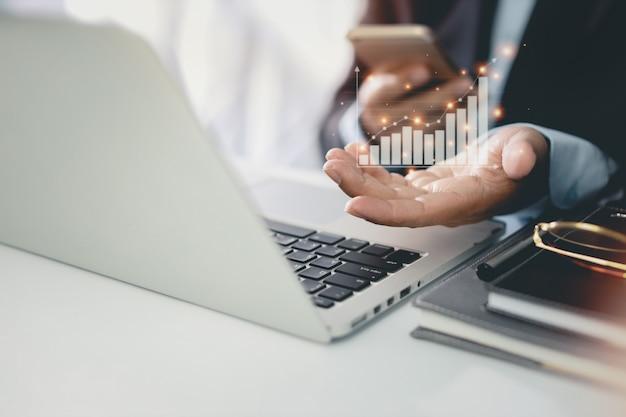 Деловой человек в черном костюме сидит и работает на компьютере и мобильном телефоне. укомплектуйте личным составом руки, показывающие рост бизнеса и успех, результат в виртуальной диаграмме с будущим растущим планом.