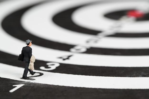 金融とビジネスの目標のダーツボードターゲットセンターのアイデアの上を歩くビジネスマン